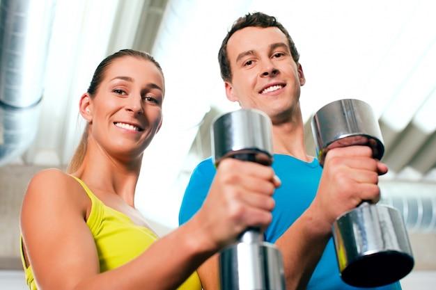 Paar im fitnessstudio trainieren mit hanteln
