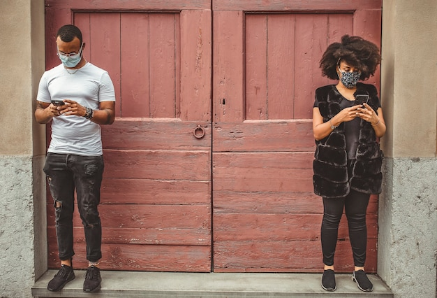 Paar im freien tragen masken mit handy