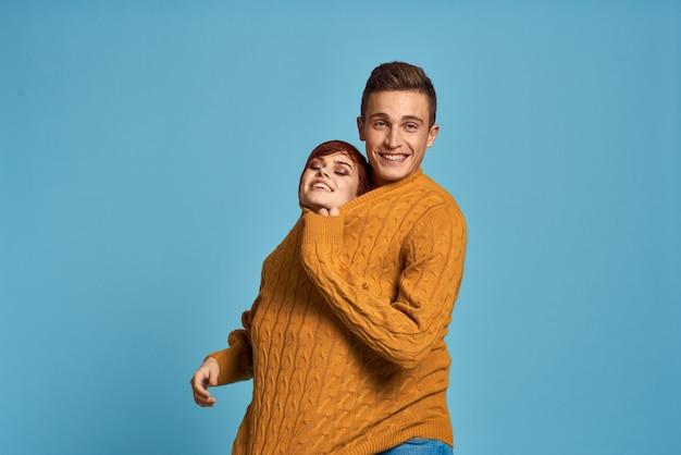 Paar im gelben pullover, der gegen beschnittene ansicht des blauen hintergrunds aufwirft. hochwertiges foto
