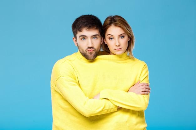 Paar im gelben pullover, der mit verschränkten armen über blauer wand aufwirft