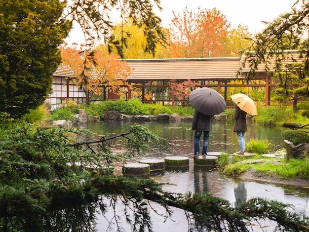 Paar im regen mit regenschirmen in einem japanischen garten. romantisches konzept.