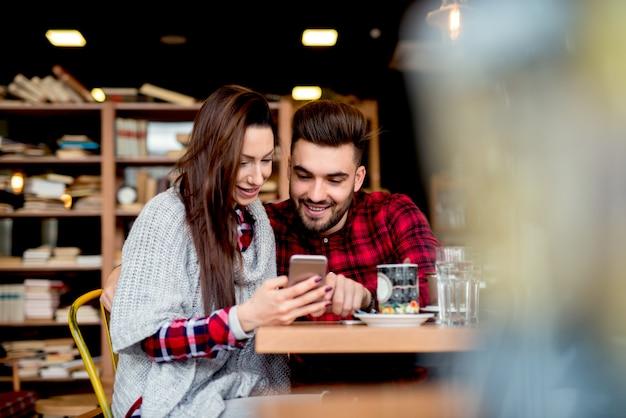 Paar im restaurant, das fotos handy betrachtet.