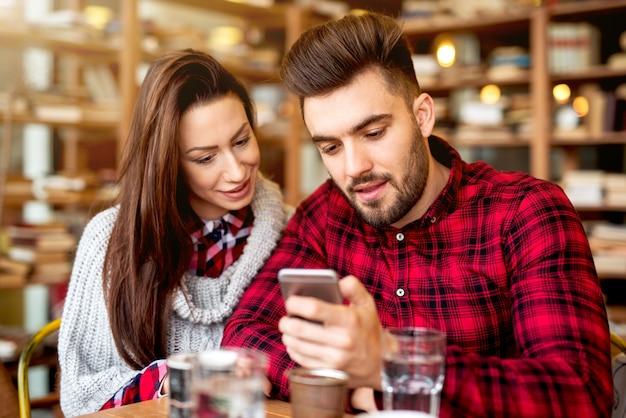 Paar im restaurant, das smartphone betrachtet.
