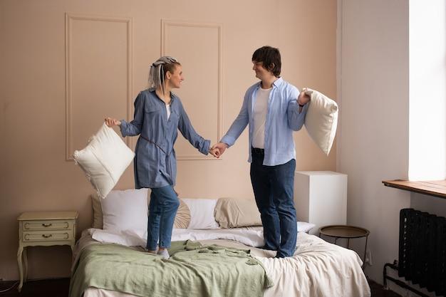 Paar im schlafzimmer mit kissen in den händen auf dem bett stehend. zeit miteinander verbringen. valentinstag feiern.