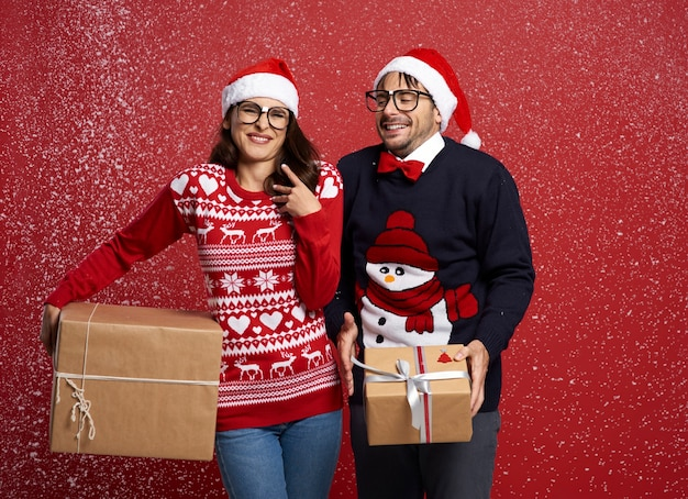 Paar im schneefall mit weihnachtsgeschenk