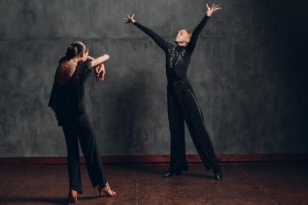 Paar im schwarzen kleid tanzen gesellschaftstanz rumba.