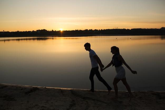 Paar im sonnenaufgang am strand
