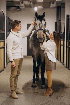 Paar im stall mit pferd