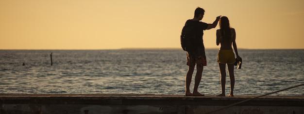 Paar im urlaub am pier bei sonnenuntergang, bannerbild mit kopienraum