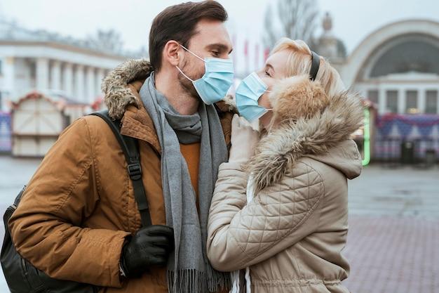 Paar im winter, das medizinische masken trägt und umarmt