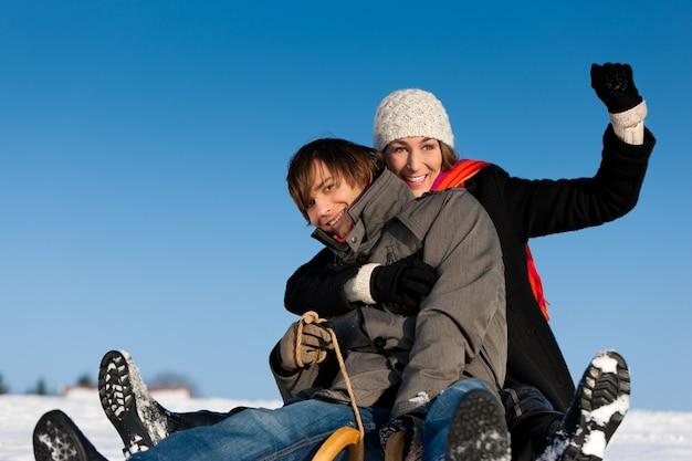 Paar im winter mit schlitten