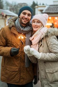 Paar im wintermann, der feuerwerk funkelt