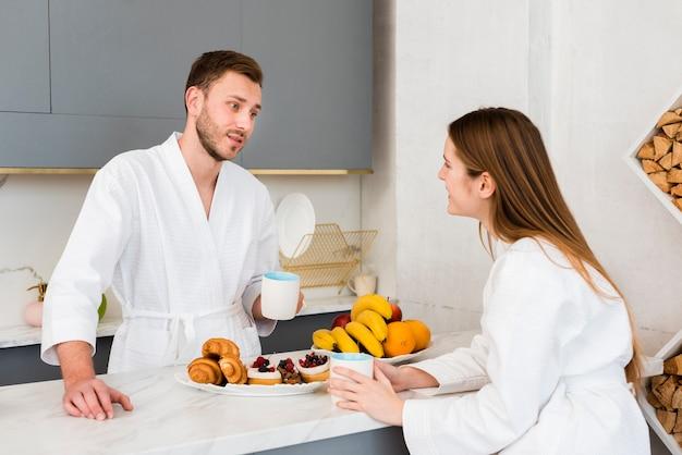 Paar in bademäntel mit kaffee in der küche