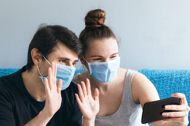 Paar in blauen medizinischen gesichtsmasken machen einen videoanruf über smartphone