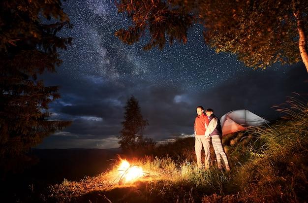 Paar in den bergen durch feuer unter sternenhimmel