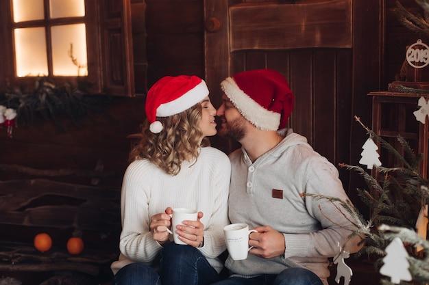 Paar in den gleichen warmen tüchern mit roten und weißen hüten bei schneewetter