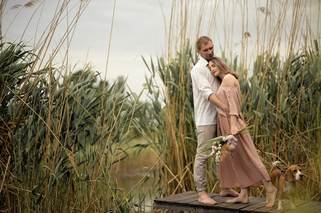 Paar in den liebesumarmungen und küssen am hölzernen pier an der natur.