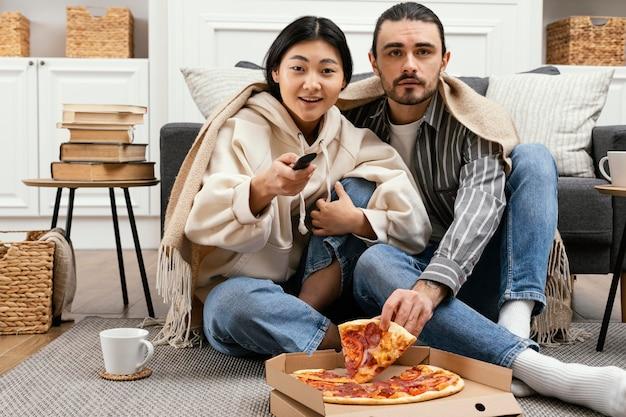 Paar in der decke, die einen film sieht
