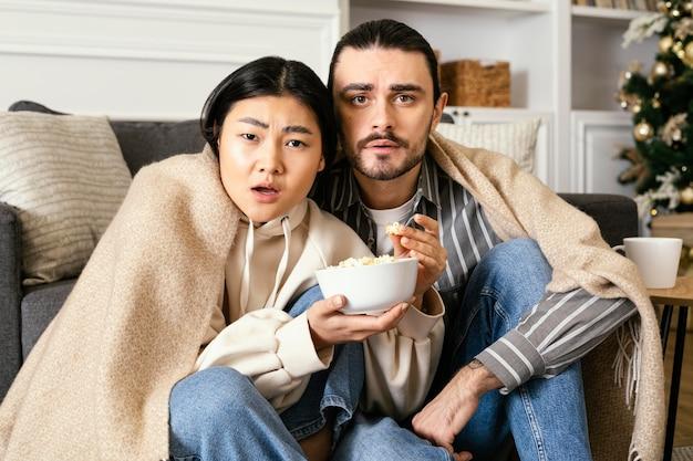 Paar in der decke, die einen gruselfilm sieht