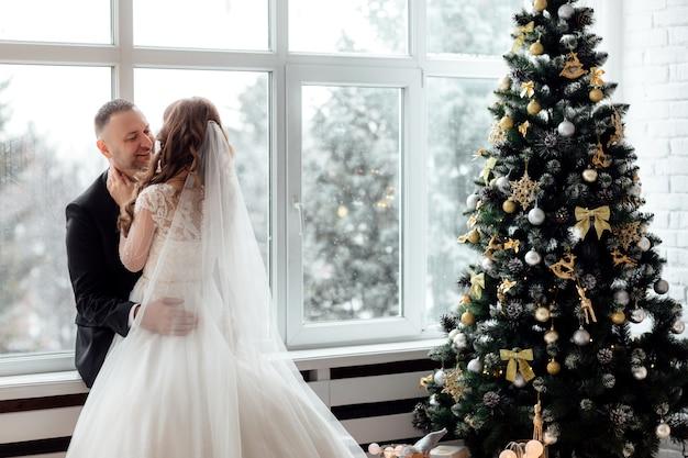 Paar in der liebe braut und bräutigam posiert im studio auf hintergrund mit weihnachtsbaum verziert