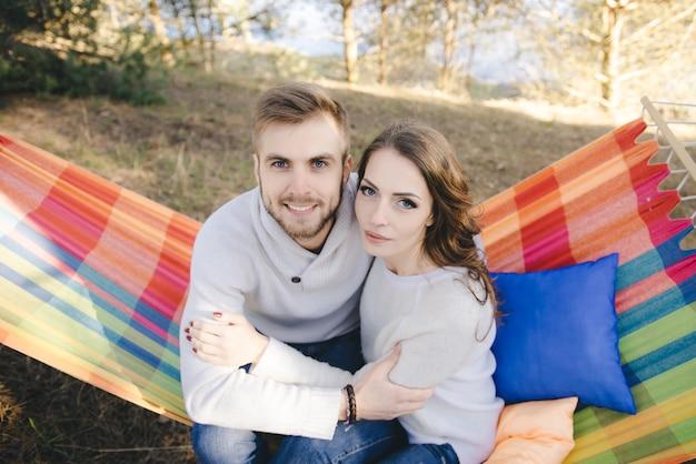Paar in der liebe, mädchen und mann in der hängematte genießt im wald, reisen liebesgeschichte konzept