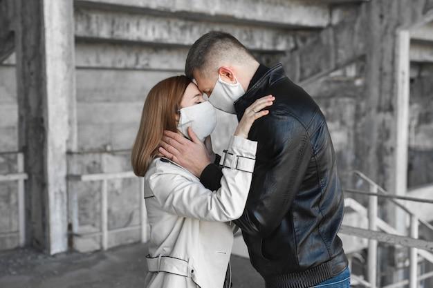 Paar in der liebe, mann und frau küssen sich in der schützenden medizinischen maske auf gesicht. kerl, mädchen gegen pandemie-coronavirus, virenschutz. covsd19