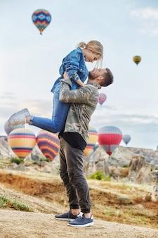 Paar in der liebe steht auf landschaft mit ballonen