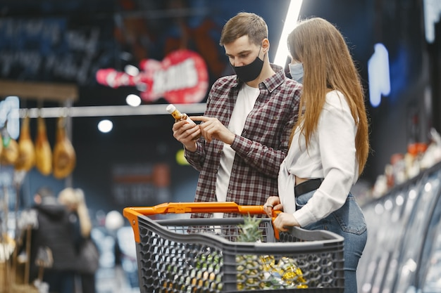 Paar in der medizinischen schutzmaske in einem supermarkt.
