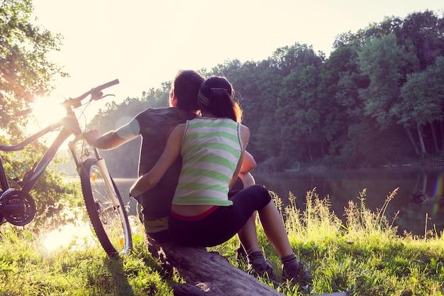 Paar in der nähe des flusses mit dem fahrrad