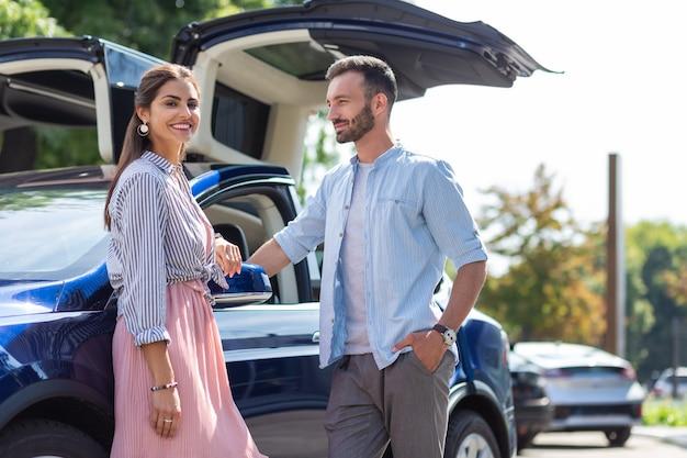 Paar in der nähe von auto. stilvolles liebespaar, das in der nähe ihres schönen luxusautos steht und den sonnigen tag genießt?