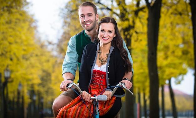 Paar in dirndl und lederhose zusammen auf einem fahrrad