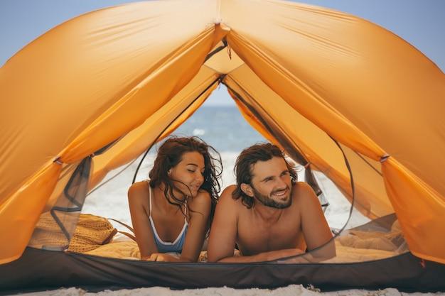 Paar in einem orangefarbenen zelt am strand