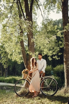 Paar in einem sommerpark. menschen mit vintage-fahrrad. mädchen in einem hut.