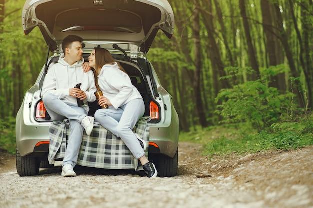 Paar in einem wald, der in einem stamm sitzt