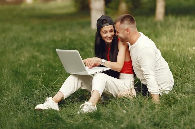 Paar in einer frühlingsstadt. dame mit einem laptop. leute sitzen auf einem gras.
