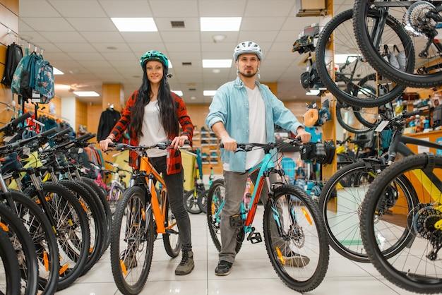 Paar in fahrradhelmen, die fahrräder wählen, einkaufen im sportgeschäft. extremer lebensstil der sommersaison, aktives freizeitgeschäft, kunden, die fahrräder kaufen