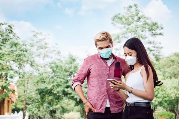 Paar in gesichtsmaske im öffentlichen park.
