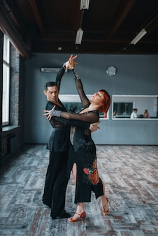 Paar in kostümen beim ballrom-tanztraining im unterricht. weibliche und männliche partner beim professionellen paartanzen im studio