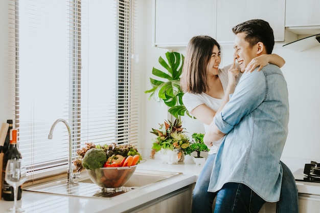 Paar in liebe lachen und spaß zusammen in der küche