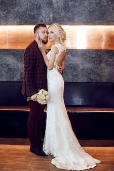 Paar in liebe umarmungen und küsse an ihrem hochzeitstag. hippie-bräutigam und die braut, liebe und loyalität. das ideale paar bereitet sich darauf vor, ehemann und ehefrau zu werden. mann und frau, die einander nah oben betrachten