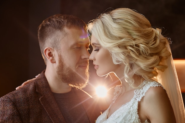 Paar in liebe umarmungen und küsse an ihrem hochzeitstag. hipster bräutigam und die braut