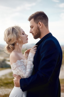 Paar in liebe umarmungen und küsse in fabelhaften bergen in der natur. frau im langen weißen kleid mit blumenstrauß in den händen, mann in der jacke. hochzeit in der natur, beziehungen und liebe