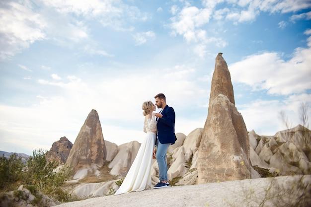 Paar in liebe umarmungen und küsse in fabelhaften bergen in der natur. mädchen im langen weißen kleid mit blumenstrauß in ihren händen, mann in der jacke. hochzeit in der natur, beziehungen und liebe