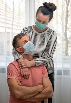 Paar in masken, die nahe fenster zu hause aufwerfen