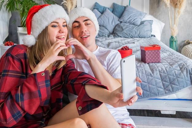 Paar in weihnachtsmützen, die zu weihnachten selfie machen und mit ihren händen ein herz machen