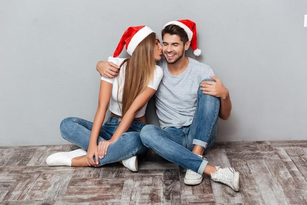 Paar in weihnachtsmützen küssen
