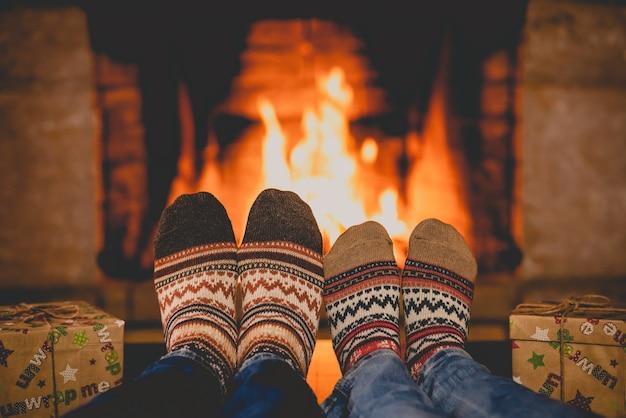 Paar in weihnachtssocken am kamin mann und frau, die zusammen spaß haben