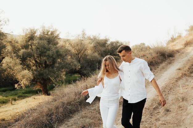 Paar in weißen kleidern, die im sommerpark gehen und sich umarmen und lächeln.