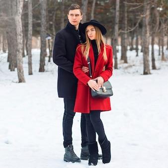 Paar in winterkleidung, die an einem verschneiten tag umarmt