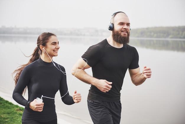 Paar joggen und laufen im freien im park in der nähe des wassers. junger bärtiger mann und frau, die zusammen am morgen trainieren